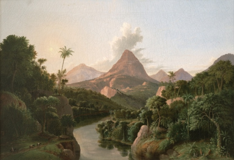A tropical landscape with a river in the foreground and several mountains in the background